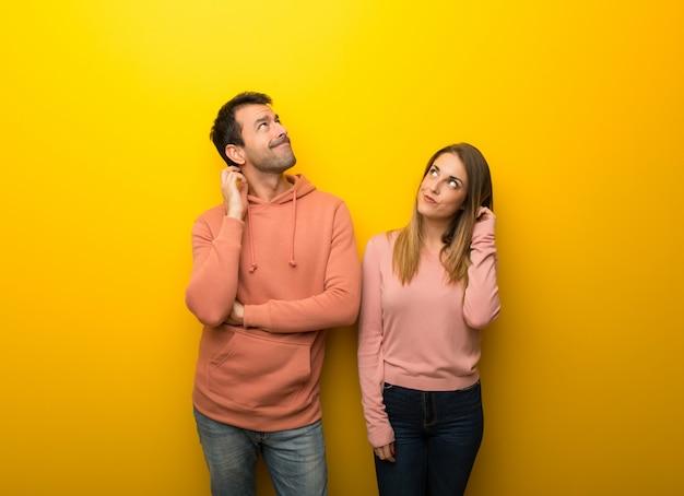 Dans la saint valentin groupe de deux personnes sur fond jaune en train de penser à une idée en grattant la tête. Photo Premium