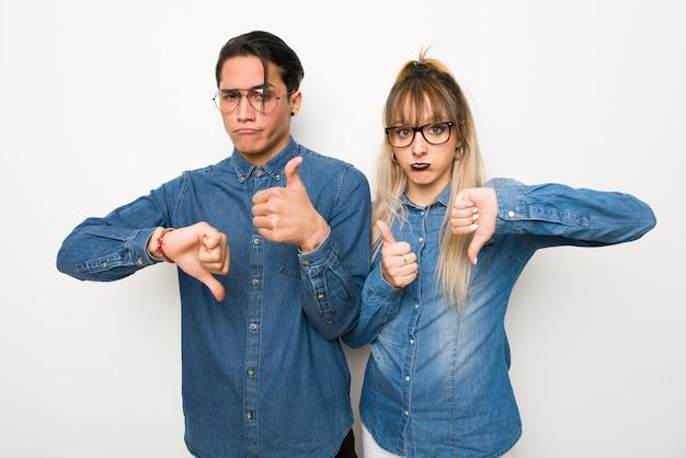Dans la saint valentin jeune couple avec des lunettes faisant bon signe. indécis entre oui ou non Photo Premium