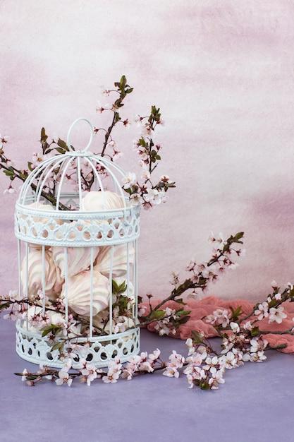Dans la vieille cage décorative se trouvent des branches de cerisier en fleurs (cadre vertical) Photo Premium