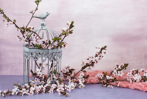 Dans la vieille cage décorative se trouvent des branches de cerisier en fleurs Photo Premium