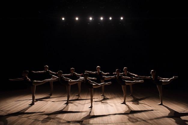 Danse chorégraphiée d'un groupe de jolies jeunes ballerines gracieuses pratiquant sur scène dans une école de ballet classique Photo Premium