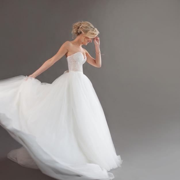 Danse jeune mariée en robe de mariée de luxe. jolie fille en blanc émotions de bonheur, de rire et de sourire, fond gris Photo Premium