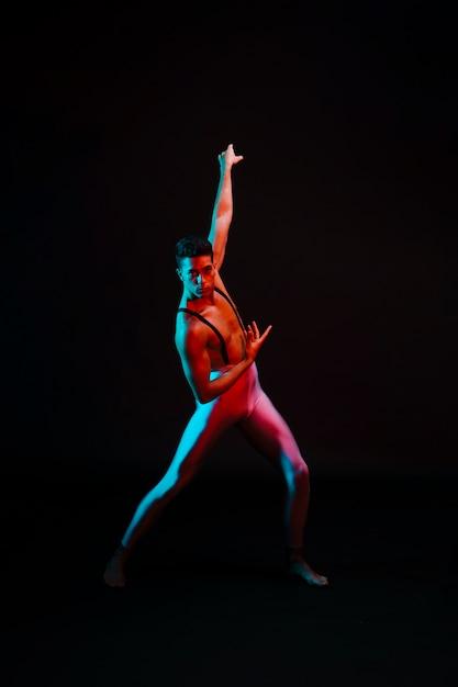 Danseur de ballet expressif dans le justaucorps debout sous les projecteurs Photo gratuit