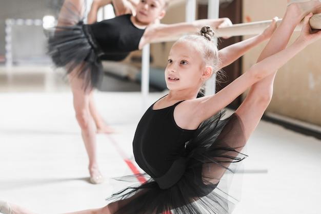 Danseur de ballet qui étire ses jambes sur la barre Photo gratuit