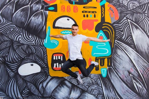 Danseur sautant sur un fond de graffiti Photo gratuit