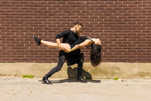 Danseur de tango sexy dansant contre le mur Photo gratuit