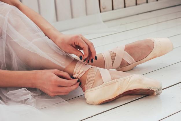Les danseurs de ballet authentiques ballerine assis sur le sol et attachant des chaussures de pointe, gros plan Photo Premium