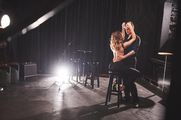 Danseurs Habiles Exécutant Dans Une Pièce Sombre Sous La Lumière. Photo gratuit