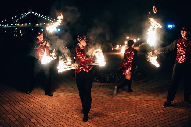 Des danseurs professionnels, hommes et femmes, présentent un spectacle de feu et une performance pyrotechnique Photo Premium