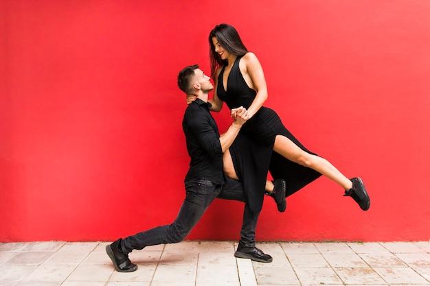 Danseurs de rue effectuant le tango contre le mur lumineux rouge Photo gratuit