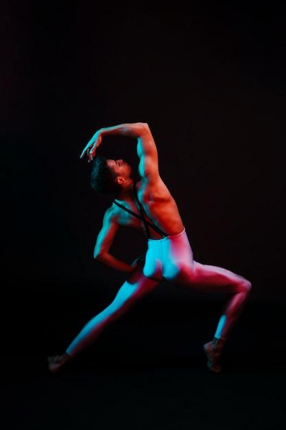 Danseuse De Ballet Méconnaissable, Cambrant Le Dos, Jambes écartées Sous Les Projecteurs Photo gratuit