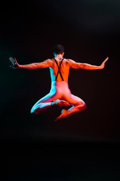 Danseuse De Ballet Méconnaissable Sautant Avec Les Bras écartés Sous Les Projecteurs Photo gratuit