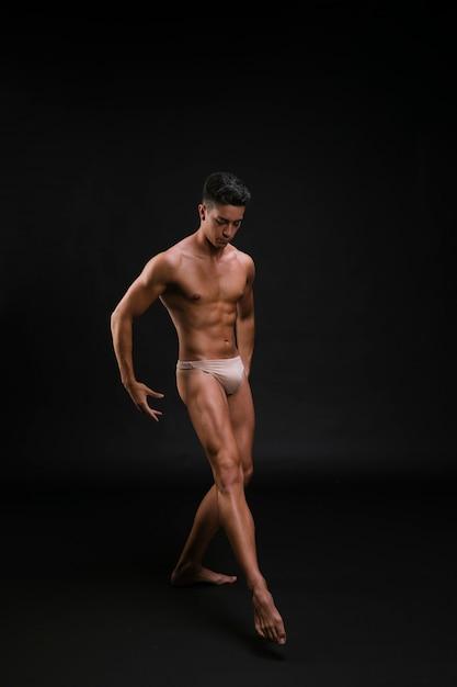 Danseuse de ballet musculaire qui s'étend d'une jambe avec élégance Photo gratuit