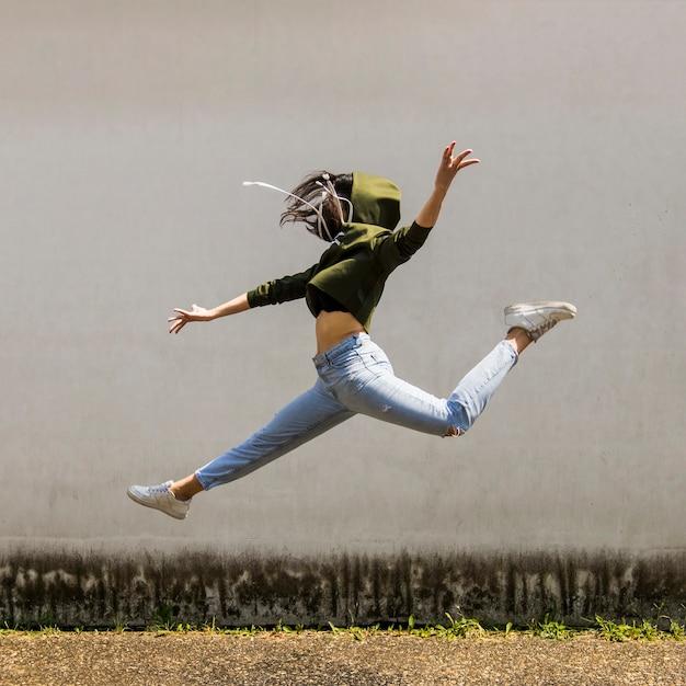 Danseuse dans le capot, sautant contre le mur Photo gratuit