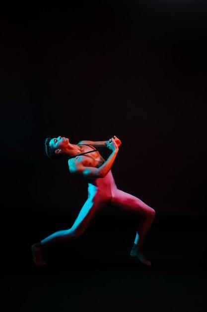 Danseuse émotionnelle Portant Un Justaucorps Jouant Sous Les Projecteurs Photo gratuit