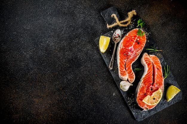 Darnes de poisson de saumon crues au citron, aux herbes, à l'huile d'olive, prêtes à être grillées Photo Premium