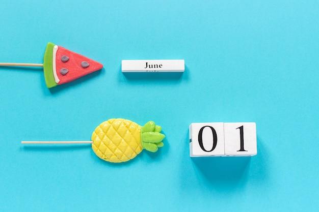 Date du calendrier 1er juin et fruits d'été ananas bonbons, sucettes au melon d'eau sur bâton. Photo Premium