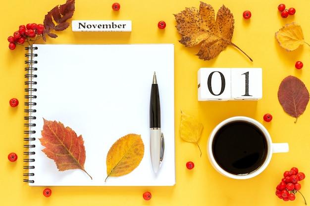 Date du calendrier, tasse de café, bloc-notes, baies avec stylo et feuilles d'automne Photo Premium