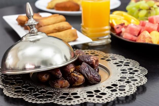 Date fruits de palme medjool, jus d'orange frais, collation samosa et fruits Photo Premium