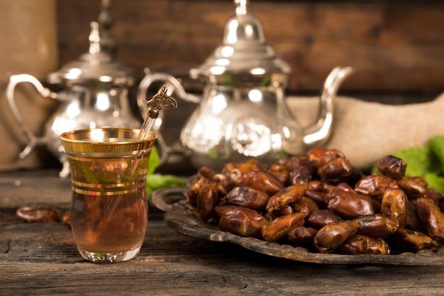 Dates fruits sur assiette avec verre à thé Photo gratuit