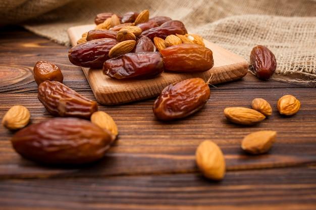 Dates fruits aux amandes sur planche de bois Photo gratuit