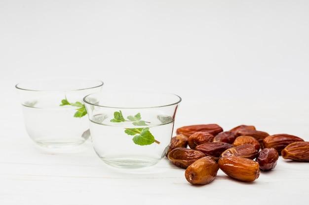 Dates fruits avec de l'eau dans des bols Photo gratuit