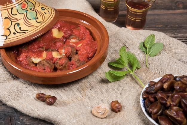Dates fruits avec viande et thé sur table Photo gratuit
