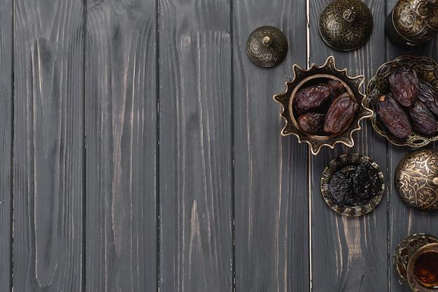 Dates juteuses sur bol turc arabe métallique sur planche de bois Photo gratuit