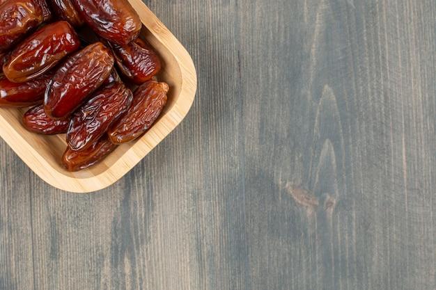 Dates Juteuses Dans Une Assiette En Bois Sur Une Table En Bois. Photo De Haute Qualité Photo gratuit