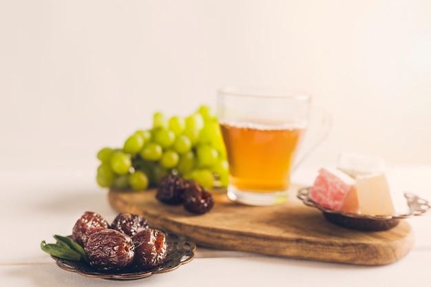 Dates sur soucoupe avec raisins de thé et délice turc Photo gratuit