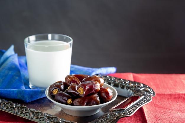 Dates et un verre de lait sur un plateau en métal - ramadan, nourriture d'iftar. Photo Premium