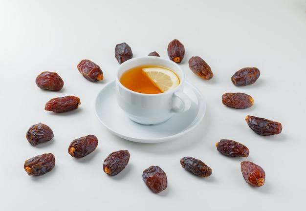 Dattes éparses Avec Une Tasse De Thé Citronné Photo gratuit