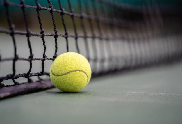 Le début d'un champion, bouchent la balle de tennis sur le fond de la cour. Photo Premium