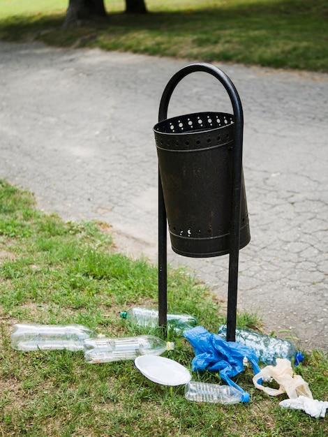 Déchets plastiques près de la poubelle métallique au parc Photo gratuit