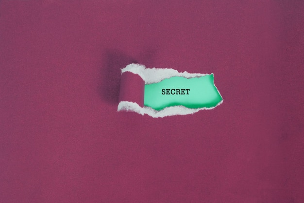 Déchirer le papier de couleur pour voir le texte secret, concept d'entreprise. Photo Premium