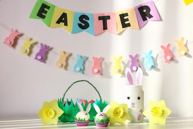 Décor de bricolage pour pâques. guirlandes en papier, lapin vase, jonquilles, lapins oeufs, panier avec des oeufs peints Photo Premium