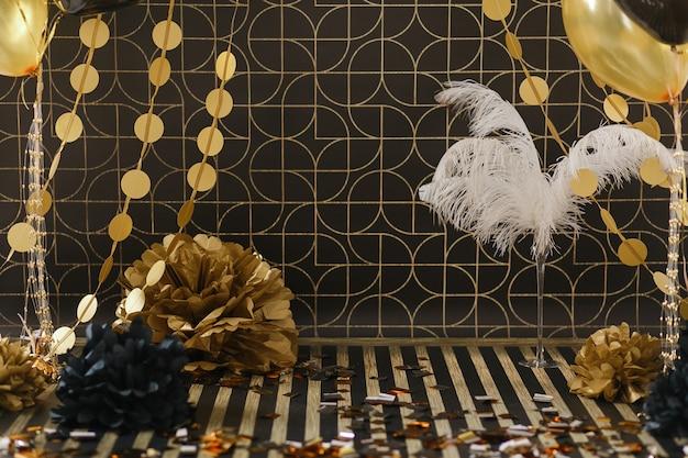 Décor de fête. décoration dorée sur fond noir avec des ballons Photo gratuit