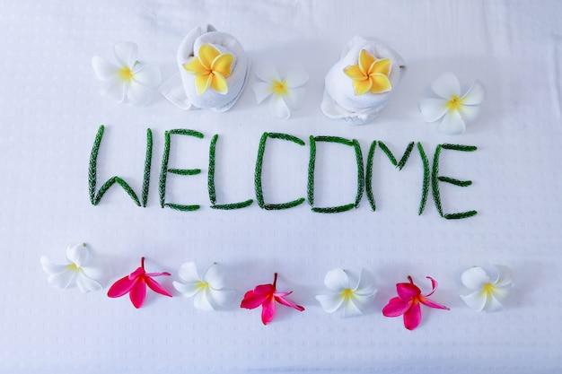 Décor floral, serviette floral et mot bienvenue sur le lit dans la chambre d'hôtel Photo Premium