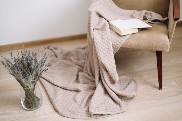 Décor à La Maison Confortable. Fauteuil Avec Une Couverture Et Un Livre, Un Vase Avec Un Bouquet De Lavande. Design D'intérieur De Maison Moderne. Photo Premium