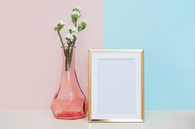 Décor à la maison moderne avec cadre photo blanc doré, vase et plante tropicale sur arr.plans bleu rose Photo Premium