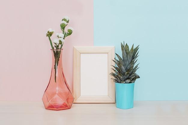 Décor à la maison moderne avec cadre photo doré, vase et plante tropicale au dos rose bleu Photo Premium