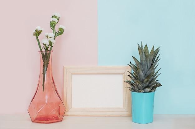 Décor à la maison moderne maquette avec cadre photo en bois, vase et plante tropicale sur ba rose bleu Photo Premium