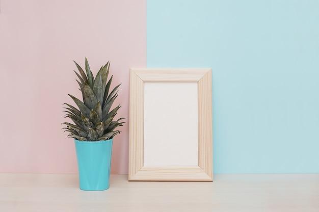 Décor à la maison moderne maquette cadre photo en bois, vase et plante tropicale sur backgro bleu rose Photo Premium