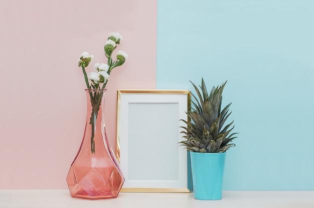 Décor à la maison moderne maquette avec cadre photo en or, vase et plante tropicale sur le dos bleu rose Photo Premium