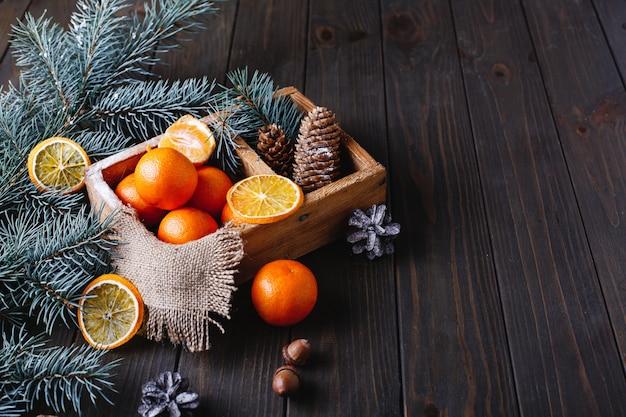 Décor de noël et du nouvel an. oranges, cônes et branches d'arbres de noël Photo gratuit