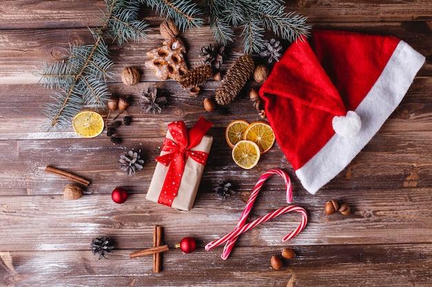 Décor de noël et du nouvel an. présenter la boîte avec le ruban rouge se trouve sur une table avec des cookies Photo gratuit
