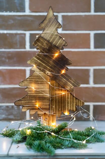 Décor De Noël Sapin De Noël En Bois Sur Le Fond D'un Mur De Briques Photo Premium