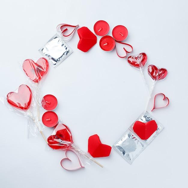 Décor rouge, douceur, coeur rouge, préservatifs sur fond blanc. Photo Premium