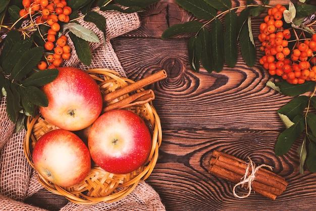 Décoration d'automne avec des branches de pommes, de cannelle et de rowan sur une table en bois. Photo Premium