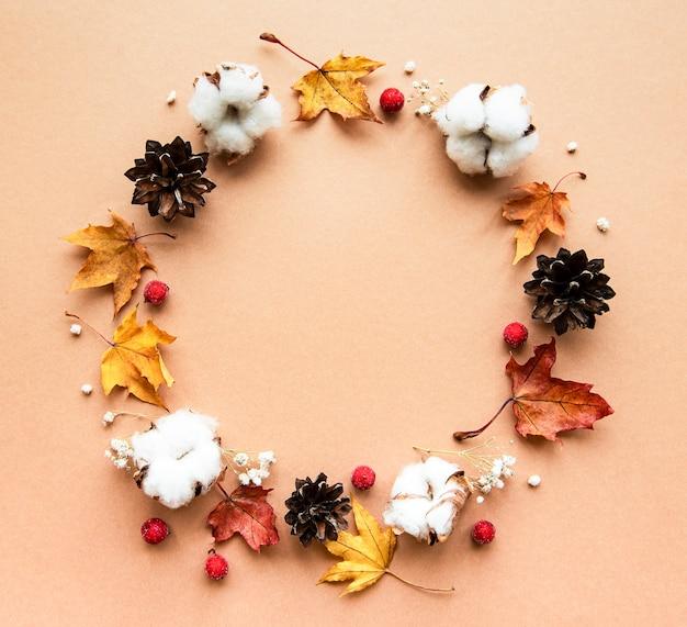 Décoration D'automne Avec Des Fleurs En Coton Et Des Feuilles D'érable Sèches En Forme De Cercle Sur Un Fond Marron Photo Premium